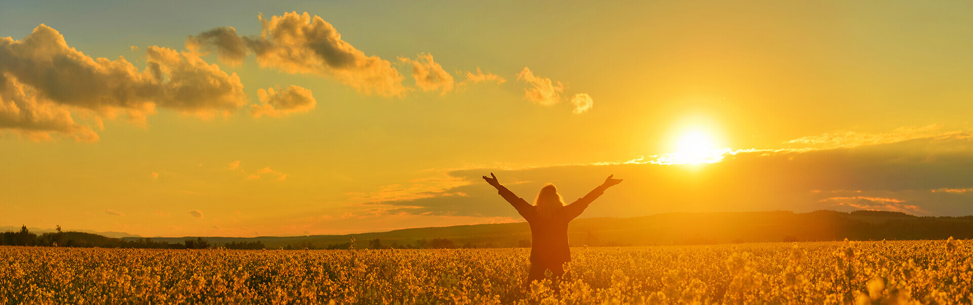 One-on-one Psych-K™ sessions Woman standing in field with arms open at sunrise